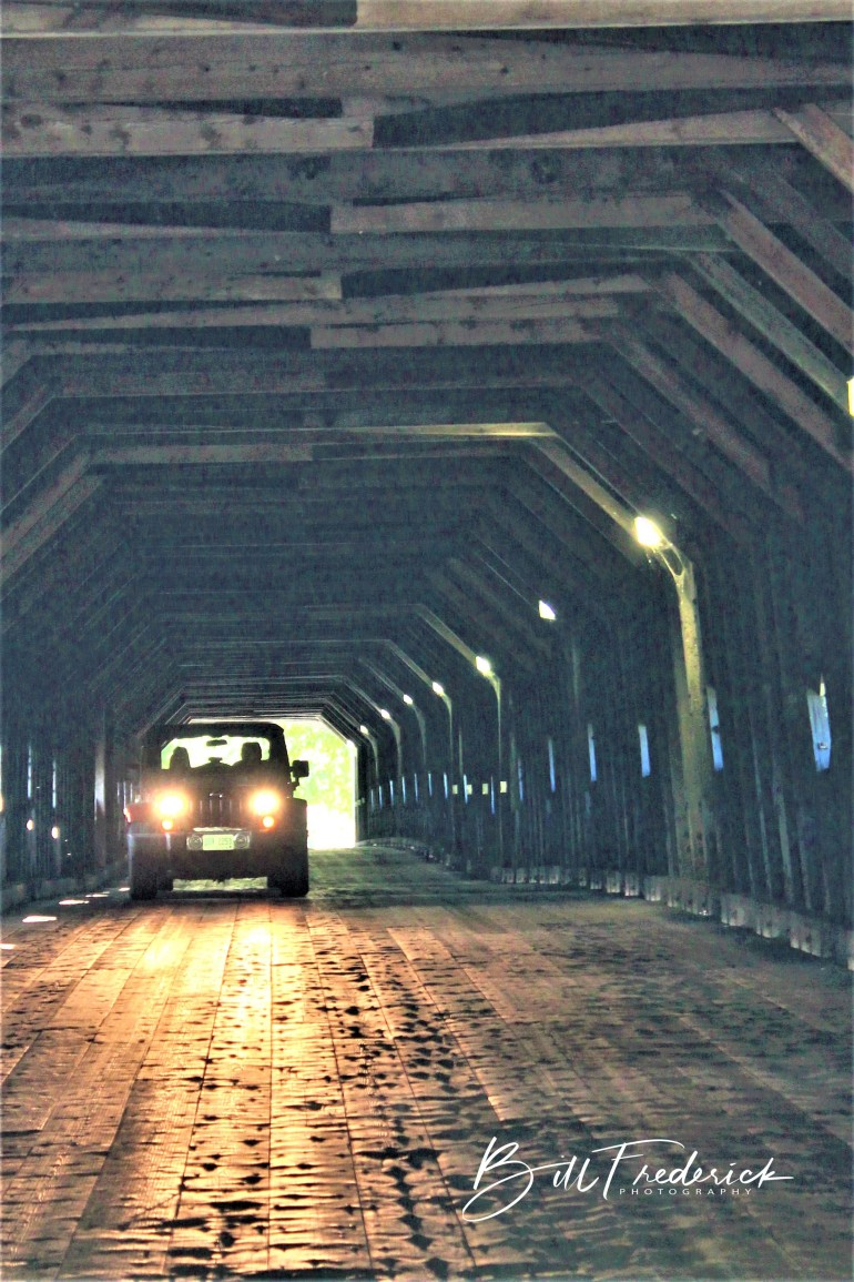 a car in covered bridge with sign