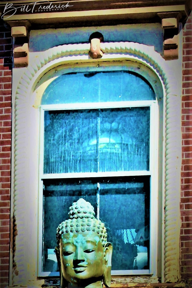 a buddha in the window with sign